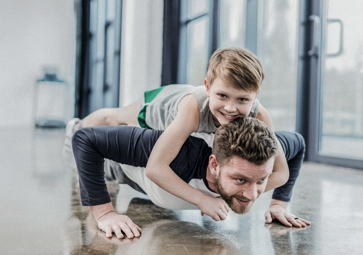 Dad doing push-ups with his son laying on top of him