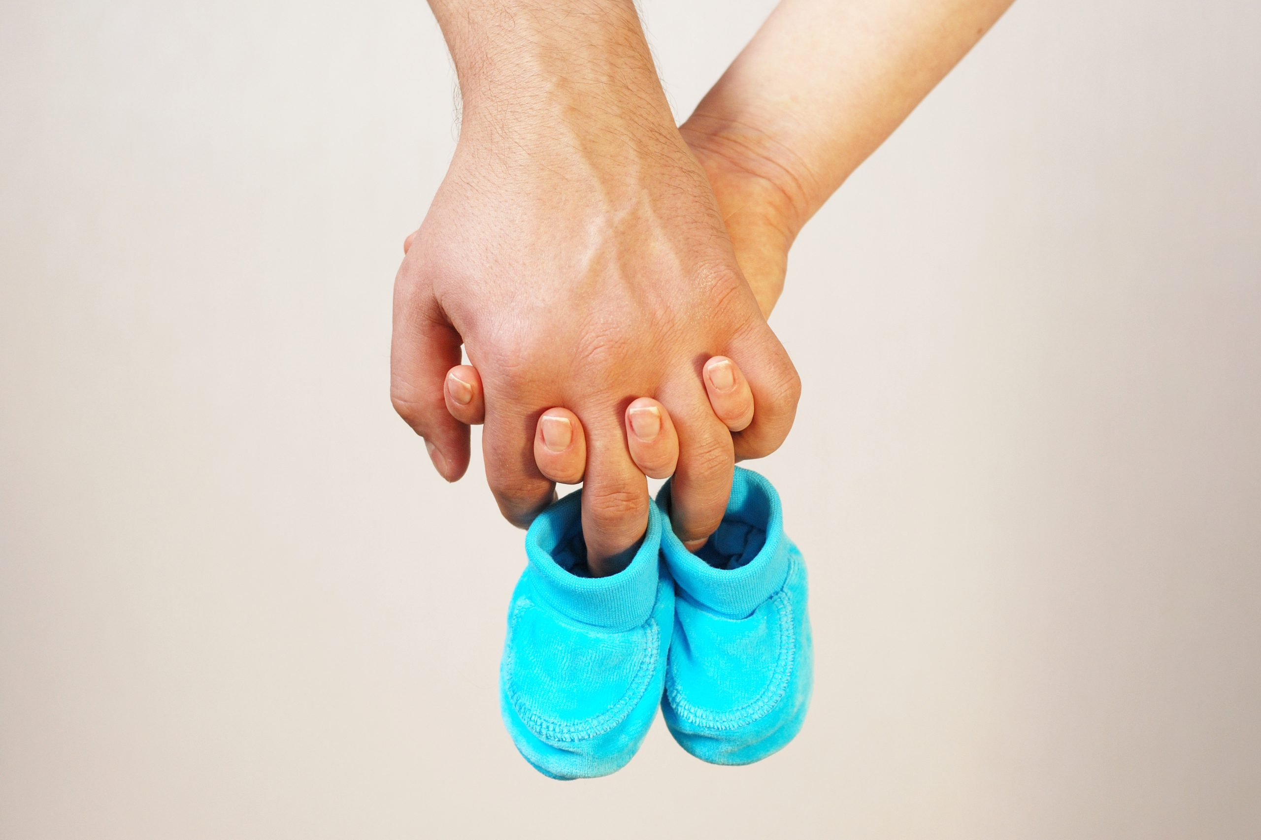 Couple holding hands and baby slippers
