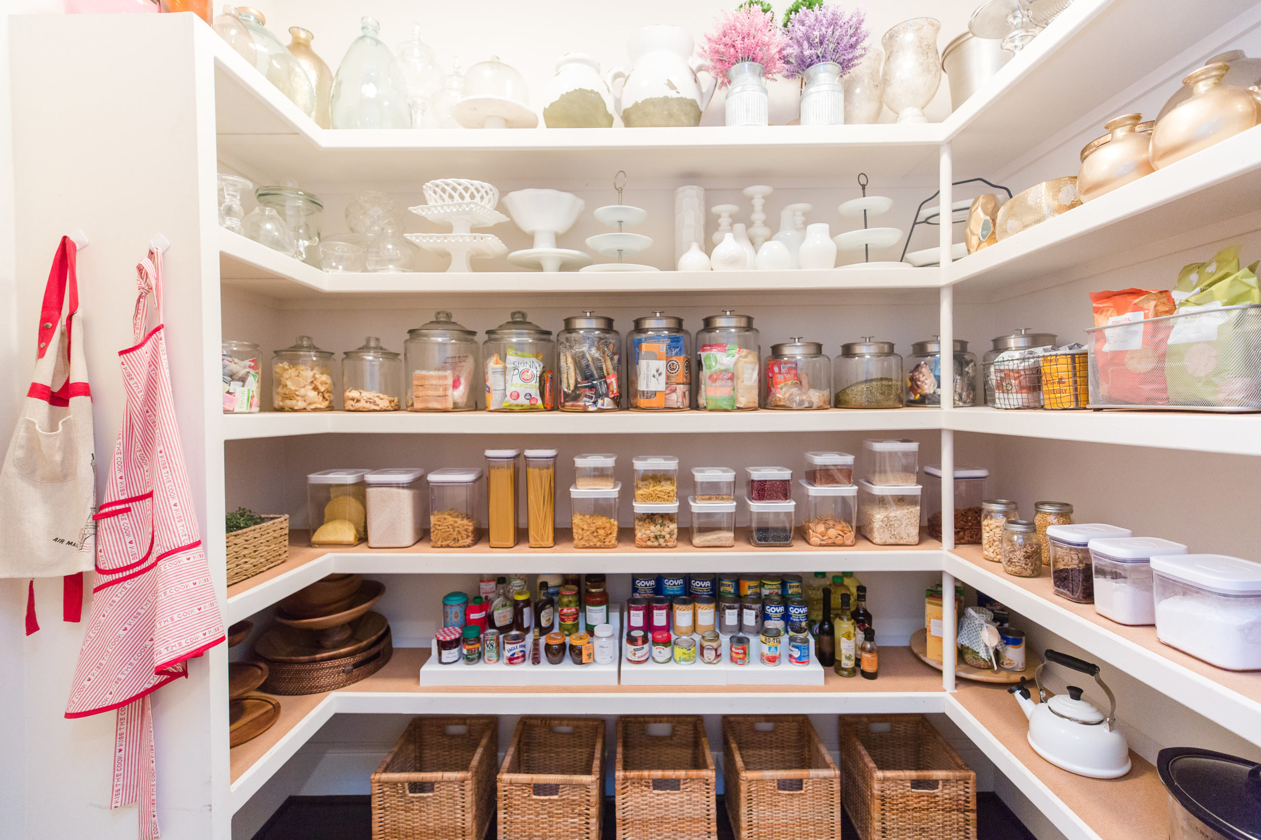 A well-organized pantry with white shelves