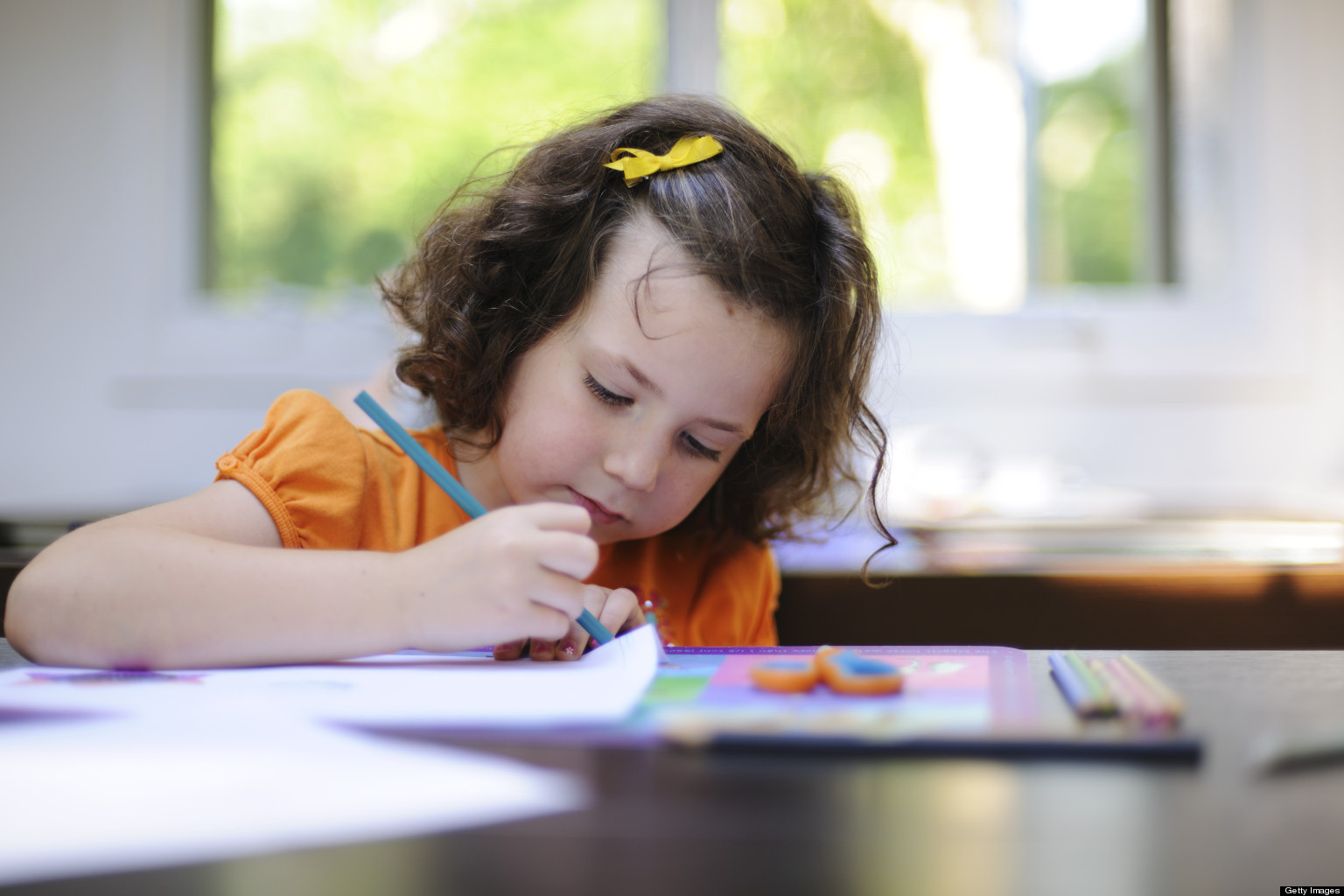 Young girl drawing with pencils