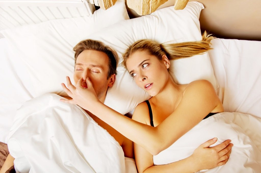 Man snoring and woman pinches his now to stop looking annoyed