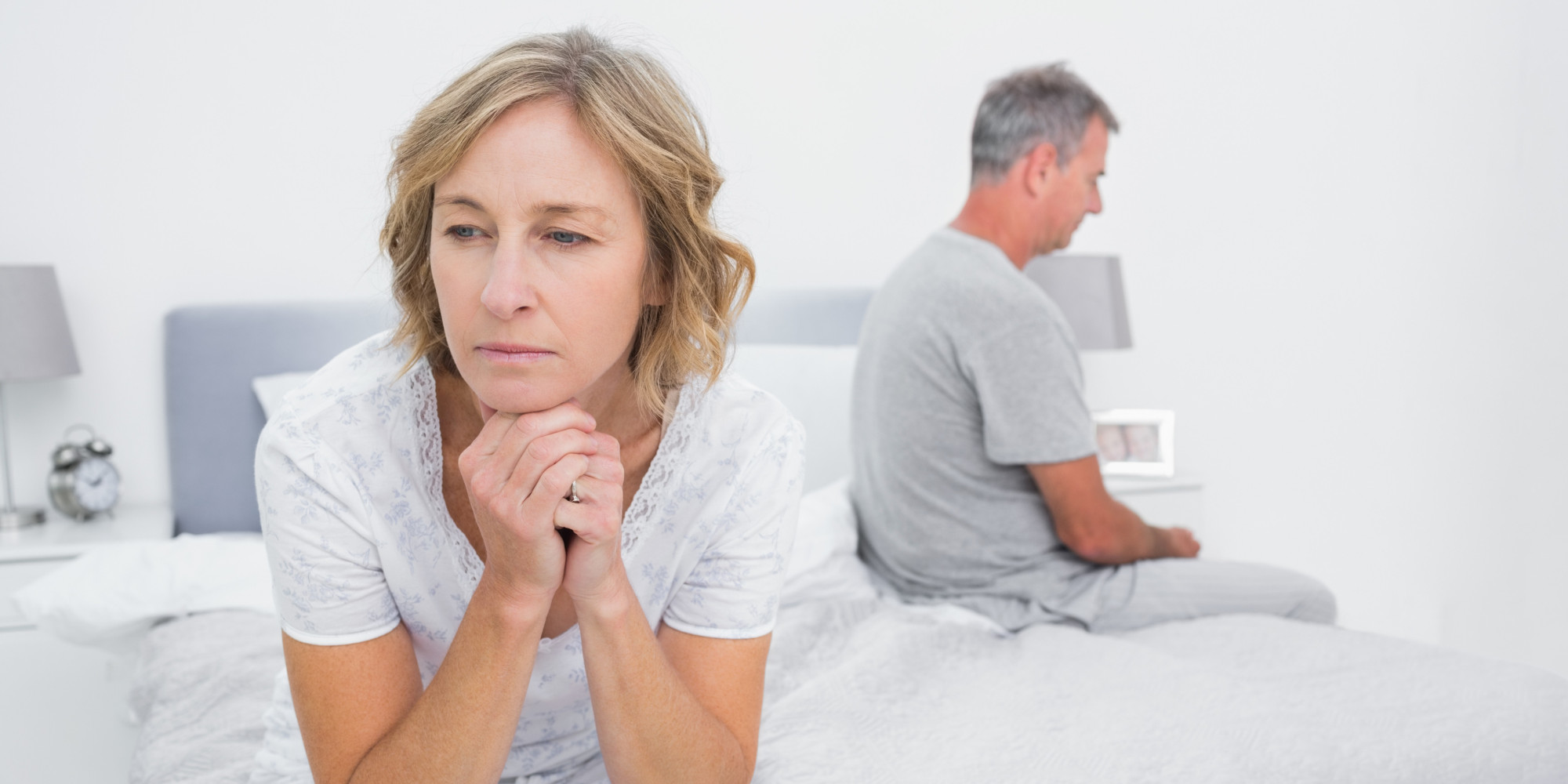 Unhappy couple over 40 sitting on different sides of bed having a dispute