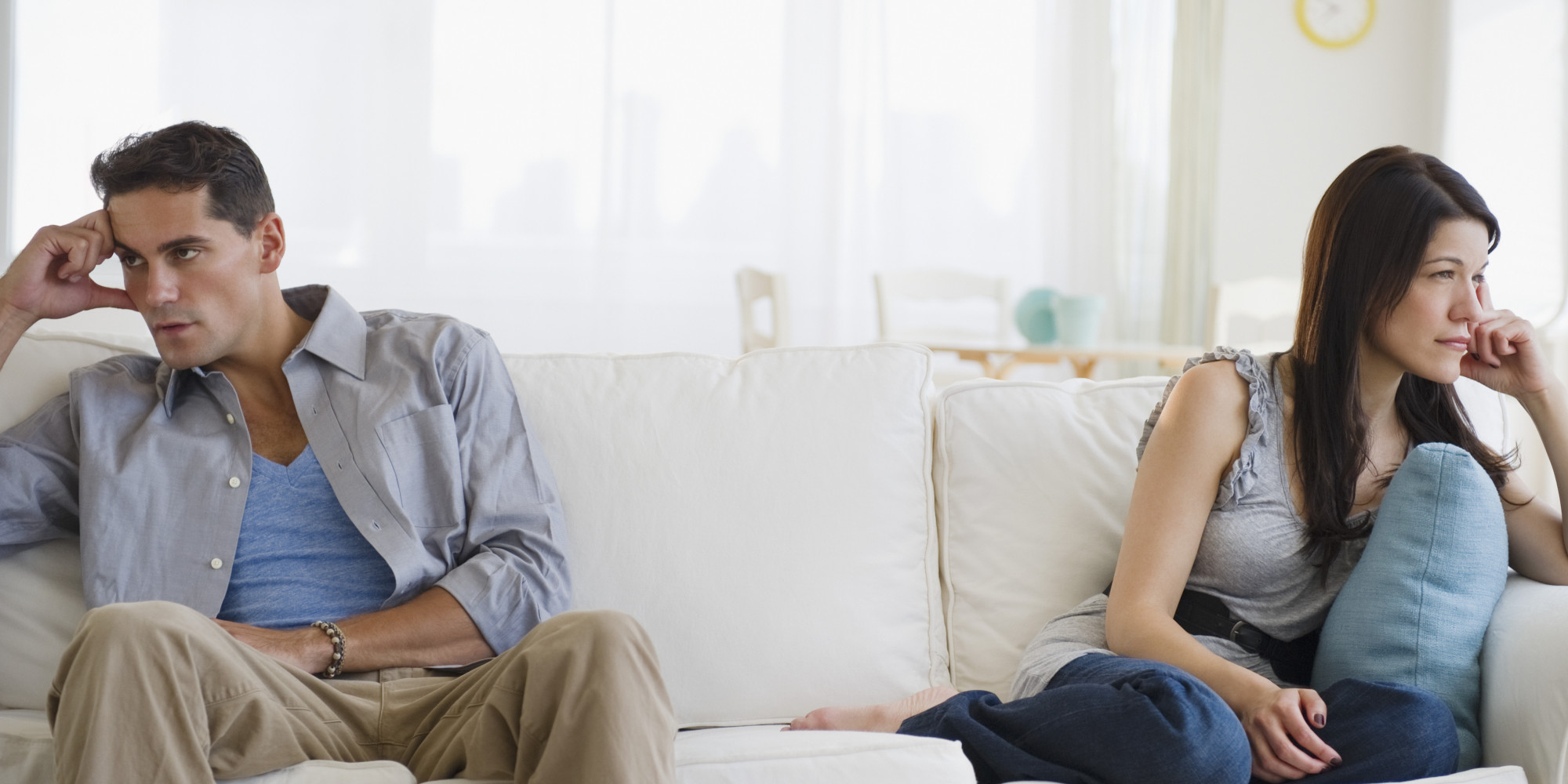 Angry couple having argument on sofa