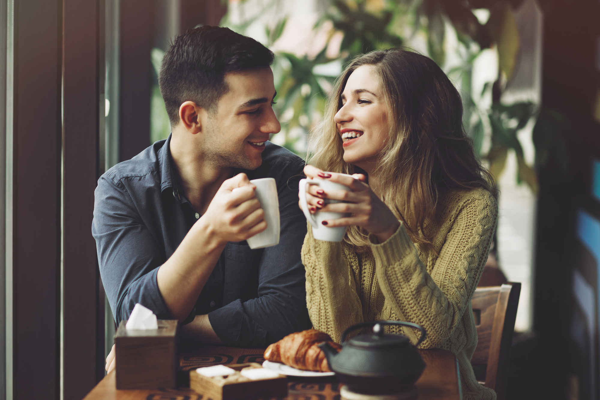 Couple in love drinking coffee and have fun in coffee shop