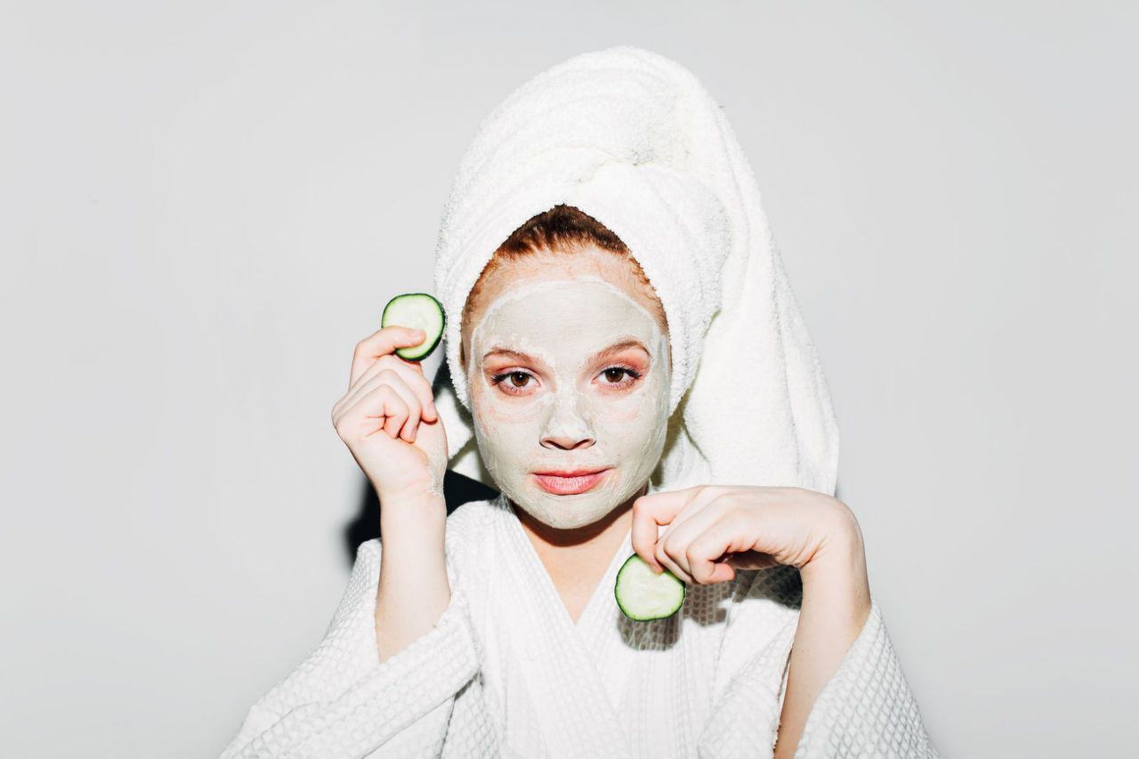 woman with towel on head, drugstore face mask, holding cucumber slices