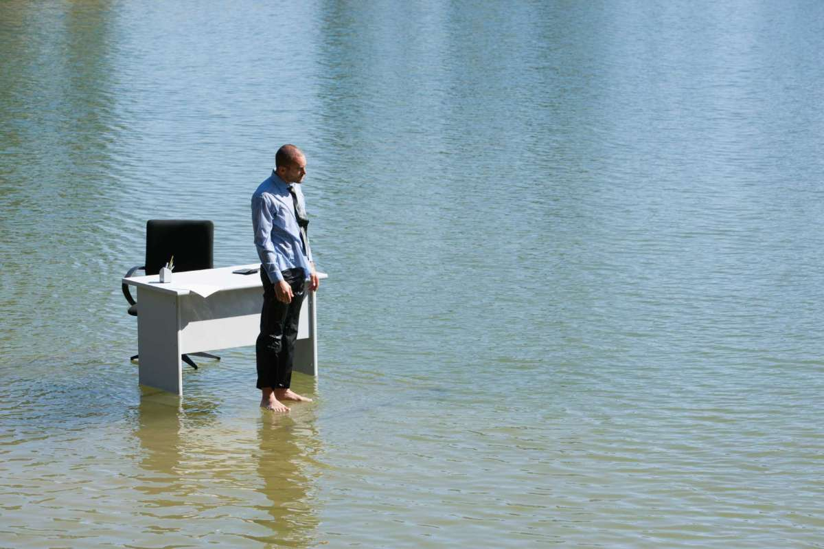 A man bear footed standing over a water body with a work desk behind him