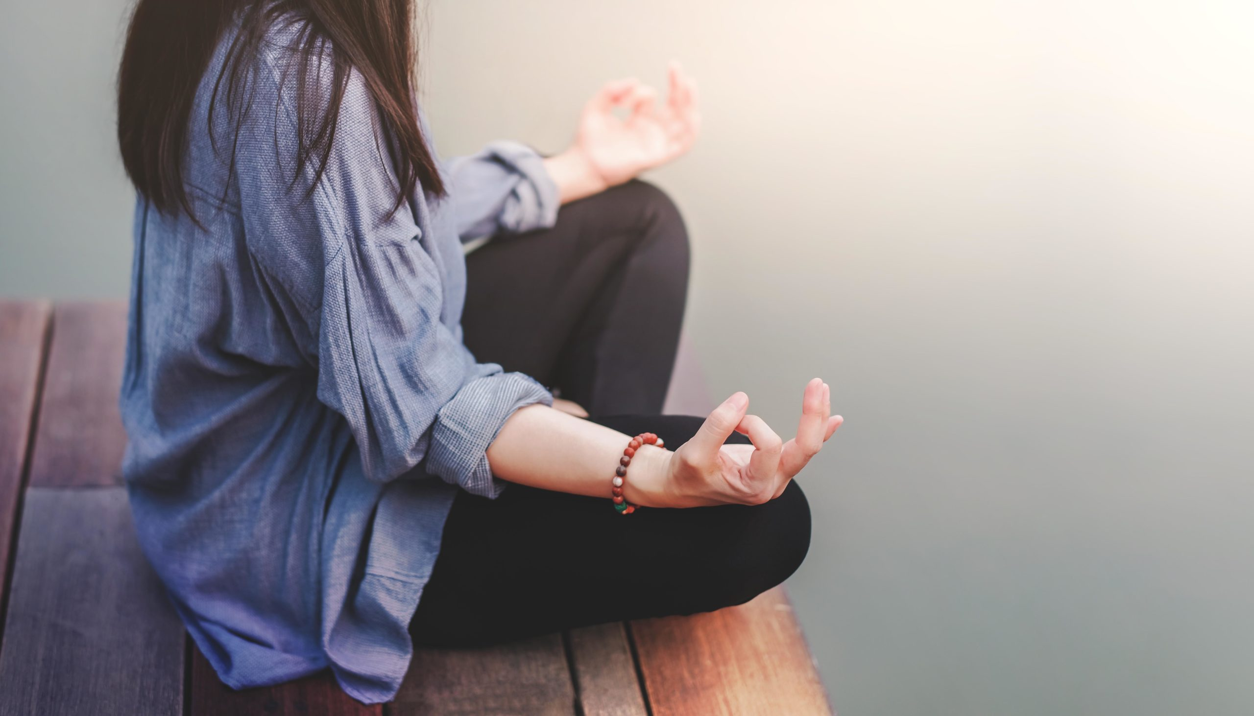 Young Woman Practices Yoga in Outdoor. Sitting in Lotus Position
