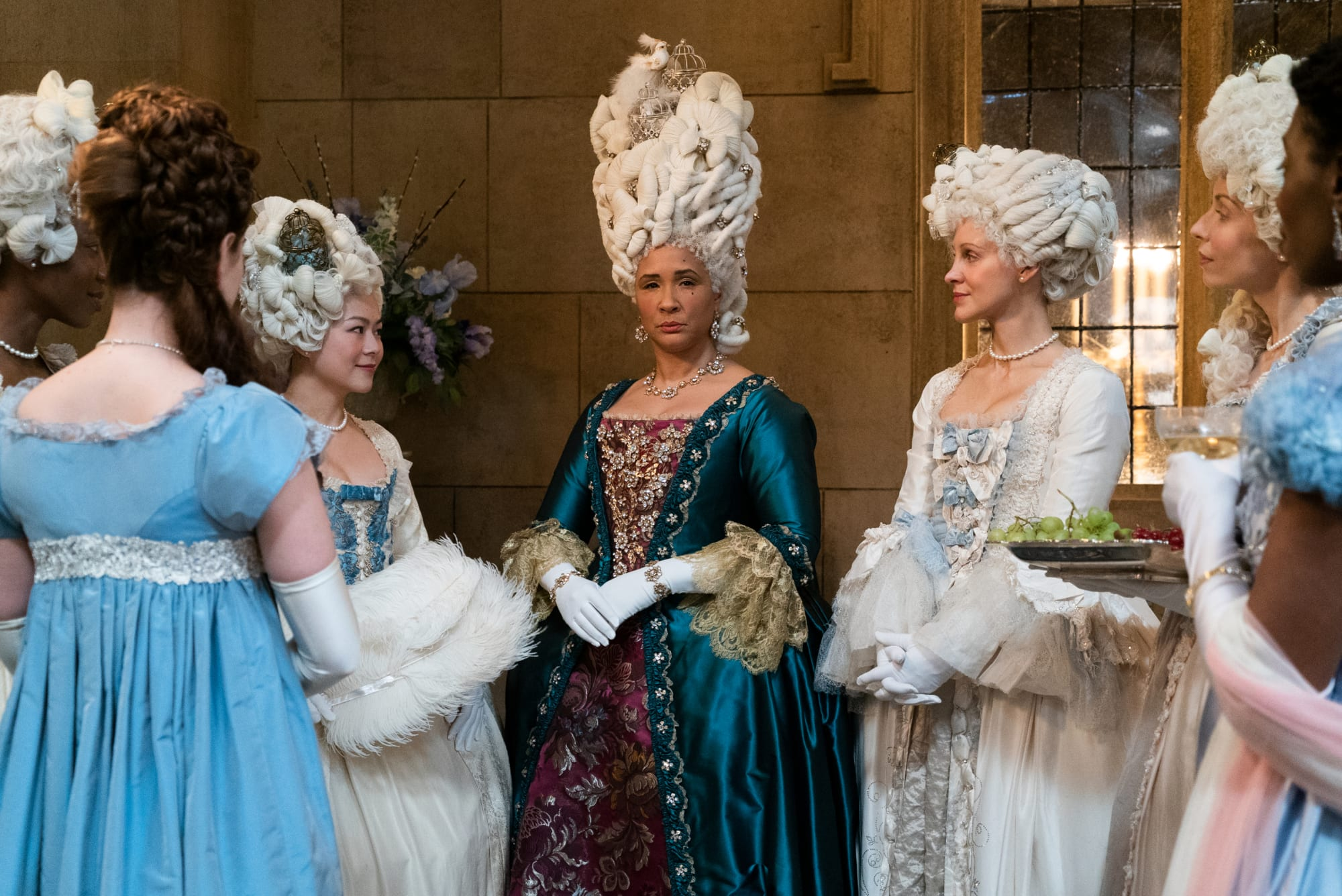 A scene from Bridgerton with the queen and her maids