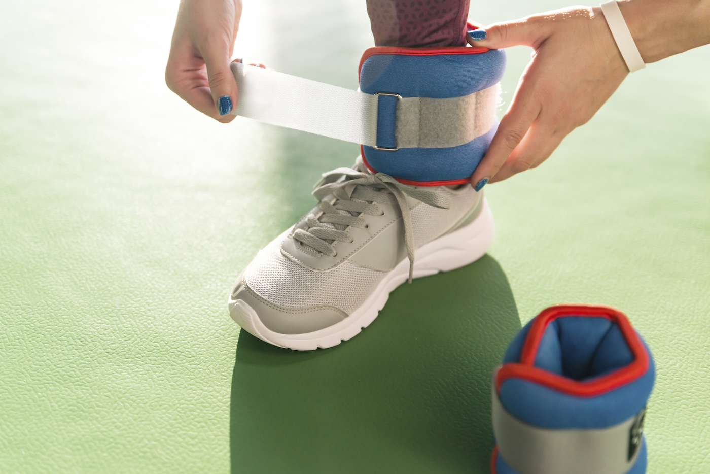 Woman putting on ankle wights before she starts a workout in a gym, health and fitness