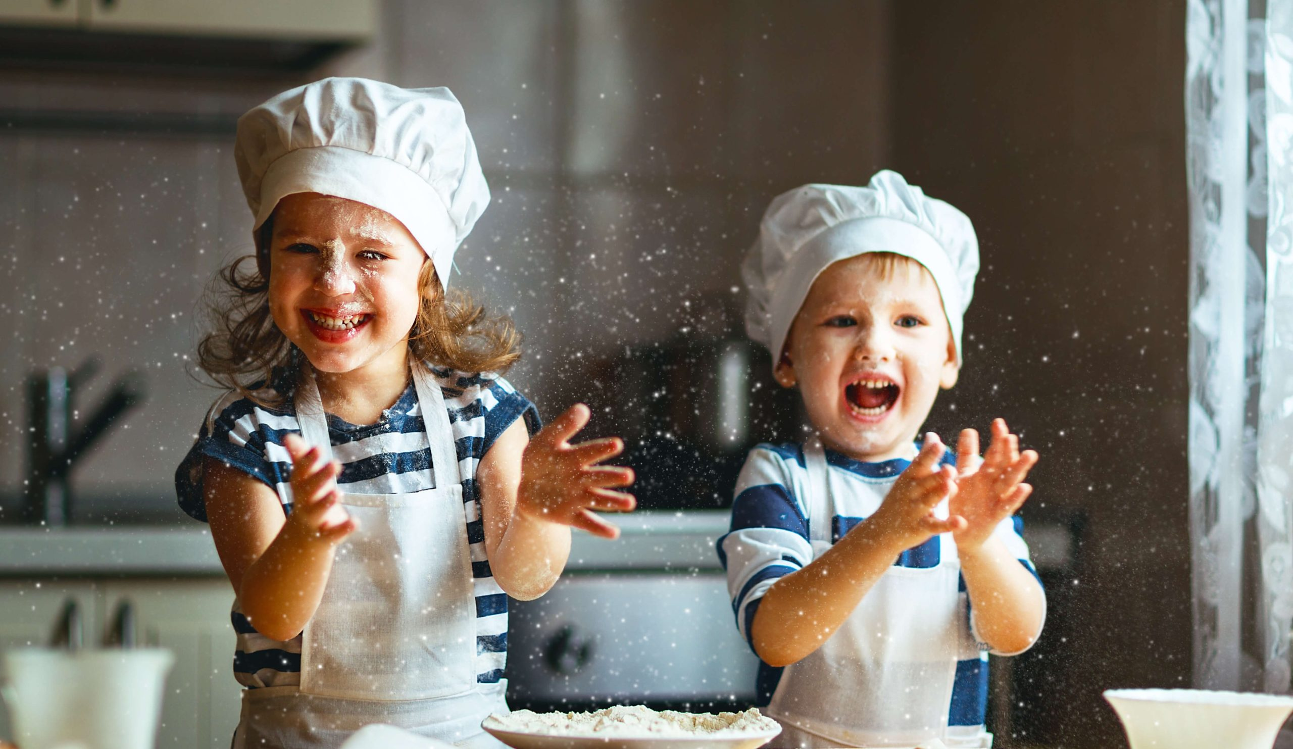Two young kids playing with flour in the kitchen