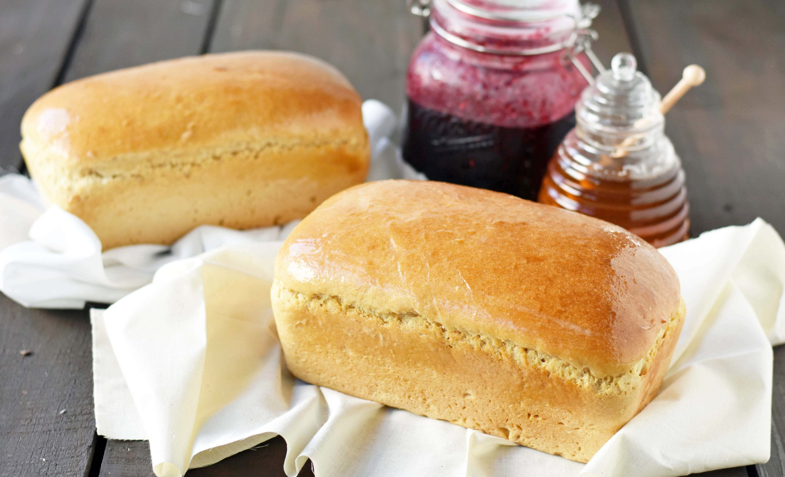 Two baked loafs of bread with jam and honey on the side