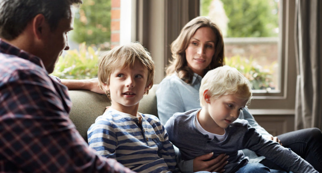 Shot of a family of four sitting together on their living room sofa